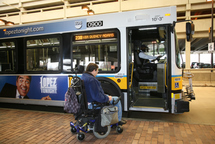 Customer in a wheeled mobility device away from front doors of low-floor bus so ramp can deploy properly.