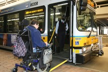 Customer in a wheeled mobility device boarding a low-floor bus using the ramp.