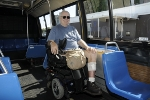 Customer in a wheeled mobility device facing foward in securement area on high-floor bus.