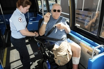 Bus Operator asking customer in a wheeled mobility device if they would like to use the lap/shoulder belt.