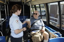 Bus Operator assisting customer in a wheeled mobility device with paying the fare.