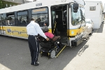 Bus Operator assisting a customer in a wheeled mobility device up the ramp of a low-floor bus.