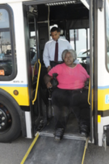 Bus Operator helping a customer in a wheeled mobility device down the ramp of a low-floor bus.