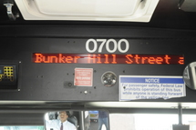 Display screen in the interior of the bus with the words Bunker Hill Street displayed.