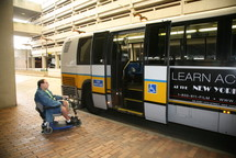 Customer in a wheeled mobility device at rear of high-floor bus.