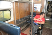 Customer using wheeled mobility device in wheeled mobility device area on commuter rail train. Click to enlarge.