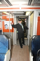 Conductor in doorway making announcement. Click to enlarge.