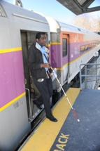 Customer using white cane to safely exit train. Click to enlarge.