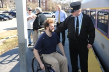 Conductor asking customer using wheeled mobility device for their destination. Click to enlarge.