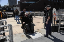 Customer using wheeled mobility device wheeling onto boat via the mobile bridgeplate. Click to enlarge.