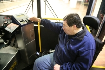 Customer in a wheeled mobility device using a CharlieCard to pay the fare.