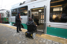 Customer who uses a wheeled mobility device near center doors of low-floor Green Line train. Click to enlarge.