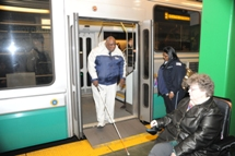 Customer with visual impairment exiting low-floor Green Line train. Click to enlarge.