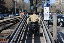 Customer using wheeled mobility wheeling to top of mini-high platform via ramp. Click to enlarge.