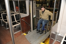 Customer using wheeled mobility wheeling onto train via bridgeplate. Click to enlarge.