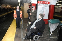 MBTA member of staff meeting customer using wheeled mobility on platform. Click to enlarge.