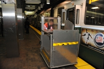 MBTA staff person positioning mobile lift in front of train doors. Click to enlarge.