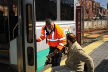 Customer using a wheeled mobility device informing MBTA staff member of their destination. Click to enlarge.