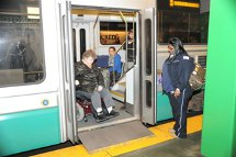 MBTA member of staff preparing to assist customer using a wheeled mobility device in exiting the train. Click to enlarge.