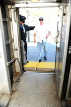 Customer using white cane boarding commuter rail train. Click to enlarge.