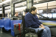 Customer in a wheeled mobility device in securement area on a low-floor bus.