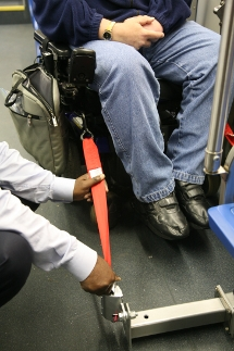 Customer in a wheeled mobility device being secured in securement area.