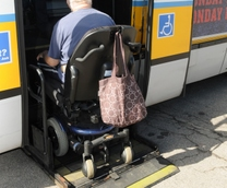 Customer in a wheeled mobility device on a lift of a high-floor bus.