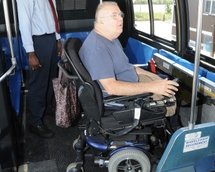 Customer in a wheeled mobility device in securement area on high-floor bus.