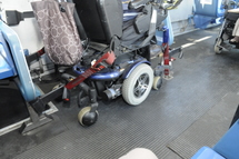 Bus Operator attaching securement straps to wheeled mobility device.