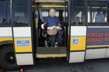 Customer in a wheeled mobility device on lift of high-floor bus.