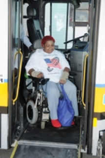 Customer in a wheeled mobility device using ramp to exit a low-floor bus.