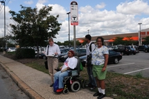 Customer in a wheeled mobility device waiting for the bus.