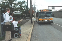 Customer in a wheeled mobility device gesturing to the Bus Operator.