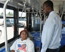 Bus Operator asking a customer in a wheeled mobility device for their destination.