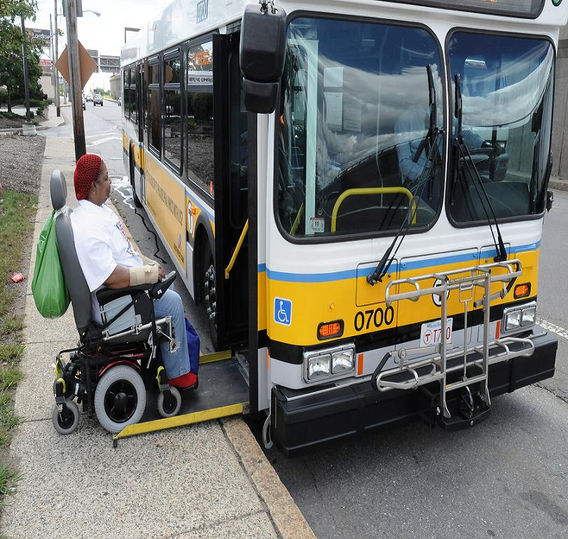Bus at curb boarding a customer in a wheeled mobility device.