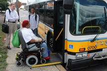 Customer in a wheelled mobility device boarding a low-floor bus before other customers.