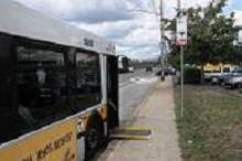 Bus lowered to curb with ramp deployed.